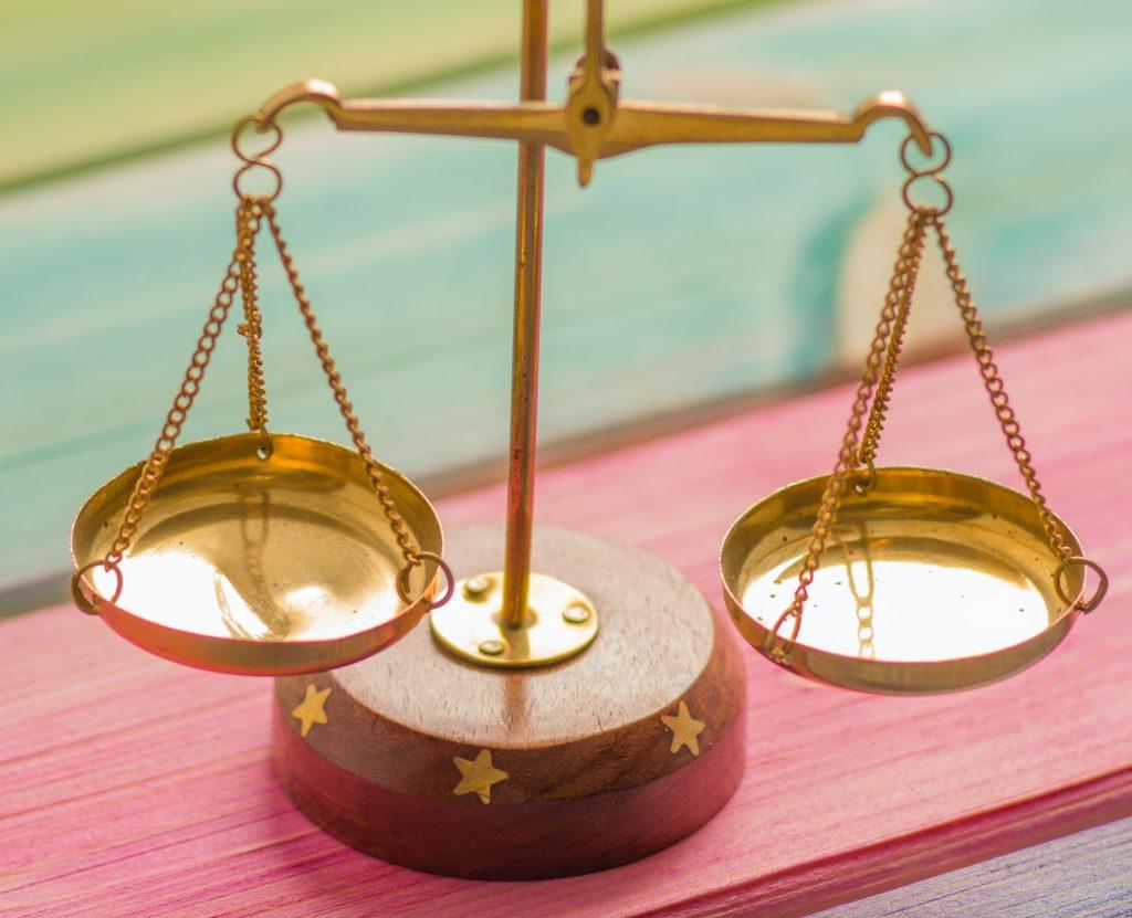 ESAT survey - work/life balance image - golden scales on pastel rainbow table