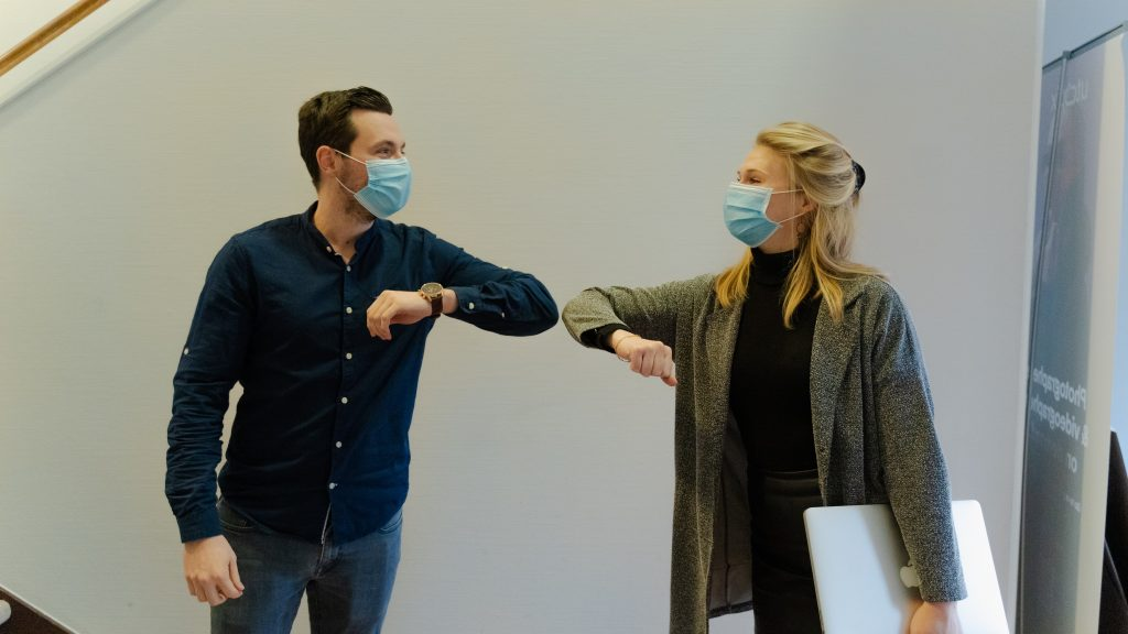 ESAT survey - management image - Man and woman in face masks touching elbows